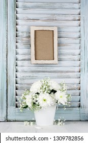 White flowers bouquet in bucket on wood table against vintage wooden shutters with empty photoframe. Shabby chic style.