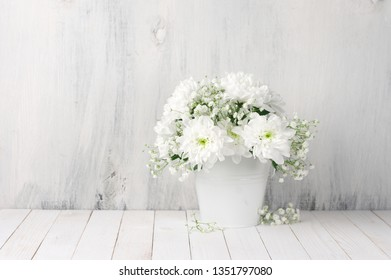 White flowers bouquet in bucket on white wood table against rustic shabby wall.