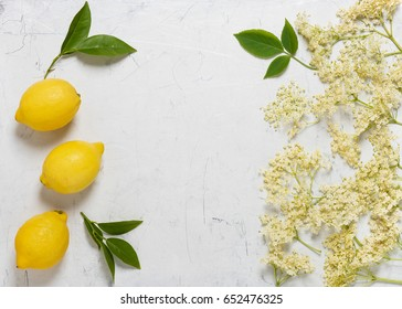 White flowers of the elder tree with lemon, ingredients for making elderflower cordial. Copy space. Top view.