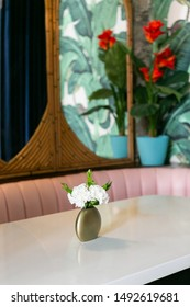 White flowers in gold vase on table at restaurant booth, pink couch, rattan mirrors and flower wallpaper