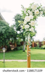 white flowers and greens on the wedding arch, rustic wedding arch decorated with flowers, stylish wedding decor