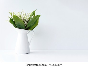 White flowers in a jar on the white background. Styled photo. Lilly-of-the-valley photo.