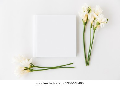 White flowers mockup with empty book.Minimalist flat lay,white background.Template for design.