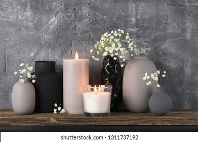 White flowers in neutral colored vases and burned candles on distressed wooden shelf against rough plaster grey wall. Home decor.