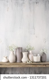 White flowers in neutral colored vases and candles on rustic wooden shelf against shabby white wall. Home decor.