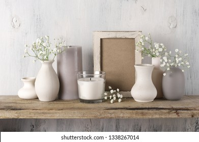 White flowers in neutral colored vases, candles and frame on rustic wooden shelf against shabby white wall. Home decor.