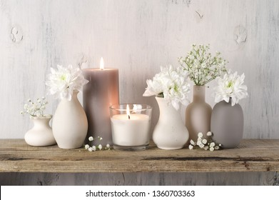 White flowers in neutral colored vases and burned candles on rustic wooden shelf against shabby white wall. Home decor.