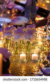 White flowers on an events table surrounded by candles.