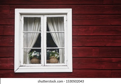 White flowers on the window of an old Finnish wooden house