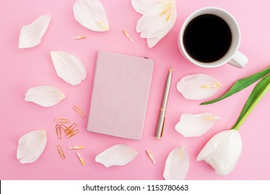 White flowers and petals with coffee mug, notebook and pen on pink background. Blogger concept. Flat lay, top view.