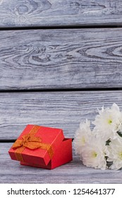 White flowers and red gift box. Red jewellery present box and white chrysanthemums on vintage wooden boards background. Saint Valentines Day concept.