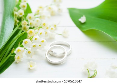 white flowers and wedding rings on bright wood table