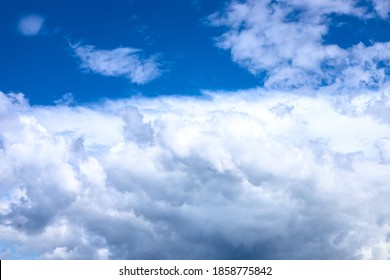 White fluffy cloud on azure blue sky. Rain weather or cyclone formation. Abstract natural photo. Cotton softness concept. Zen or relax cover template.  Cloudy sky overcast