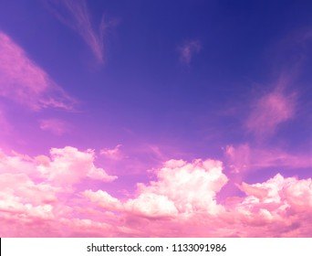 White fluffy clouds in deep blue sky with purple and pink color light