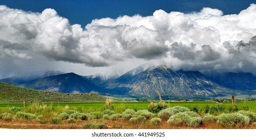 white fluffy clouds rolling down the sierra nevada mountains with green farmland valley in foreground