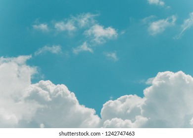 White fluffy clouds in turquoise blue sky. Copy space. Vintage colors. For background and wallpaper