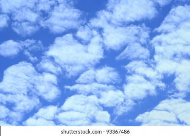 White Fluffy evenly distributed clouds on blue sky.