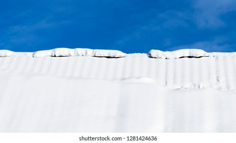 a lot of white fluffy snow with bumps on the roof of the house