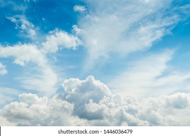 White fluffy thick clouds against the blue sky. Natural background wallpaper. The concept of clean air and ecology.