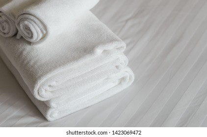 white fluffy towels on bed in hotel bedroom. Close up view