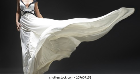 White fluttering dress on black background