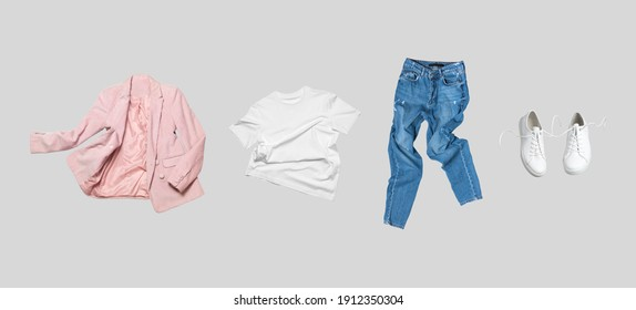 White flying cotton T-shirt, blue jeans, white leather sneakers, fashionable pink blazer jacket isolated on gray background. Clean Branding clothes. Mock up for your design. Spring Summer Clothing