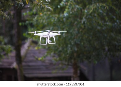 White flying quadrocopter with camera on green forest background