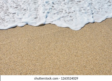 White foam on a sandy beach. Copy space.