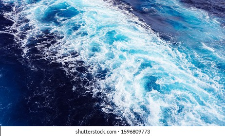 White foam sea wave. sea foam in the Pacific Ocean, the bright color of the water is turquoise, blue. deep marine texture. dark clear water in the ocean