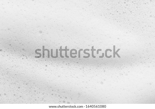 White foam texture background. Cleanser, soap, shampoo bubbles closeup. Foamy skin care product sample
