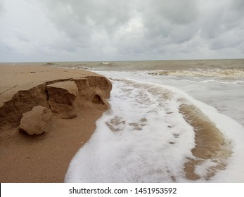 the white foam wave hit the sand shore and slowly do erosion to the beach with cloudy sky as to show the sea in monsoon season that is not a good time to travel,  but the price will be really cheap.