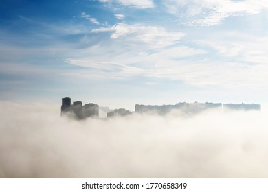 White fog in the city, residential buildings in mist against the blue sky with clouds. Urban landscape in early morning, beautiful background for wet weather