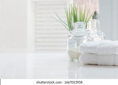 Weiße gefaltete Handtücher und Glasflasche auf weißem Tisch mit Kopienraum auf unscharfem Hintergrund im Badezimmer. Für Produktdarstellung-Montage.
