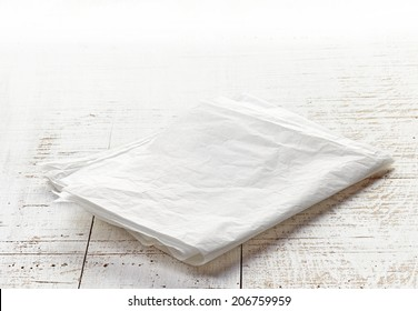 white folded wrapping paper on wooden table