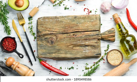 White food background: spices, herbs and vegetables on a white wooden background. Top view. Free space for your text.