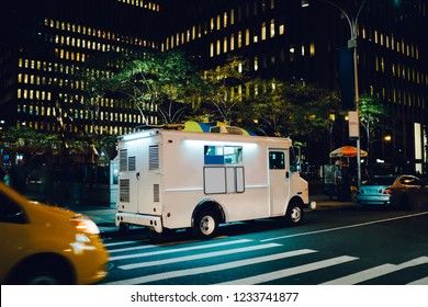 White food truck parked on city street near buildings using for retail business startup, Van automobile with mock up copy space area for brand name selling ice cream parked in urban setting at night