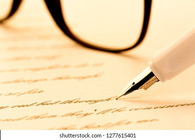 white fountain pen writing a letter, glasses