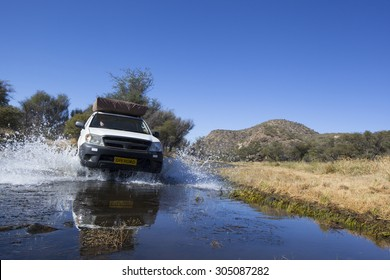 white four by four car crossing a river with splashing water, Travel concept for off-road adventure and fun in a south  african landscape