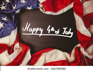 White fourth of July graphic against chalkboard and american flag