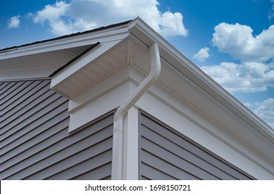 White frame gutter guard system, with gray horizontal vinyl siding fascia, drip edge, soffit, on a pitched roof attic at a luxury American single family home neighborhood USA
