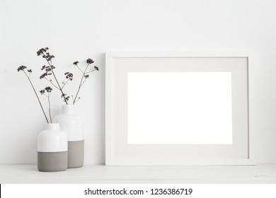 weißer Rahmen, verstaut und trockene Zweige in Vase auf Buchregal oder Schreibtisch. Weiße Farben.