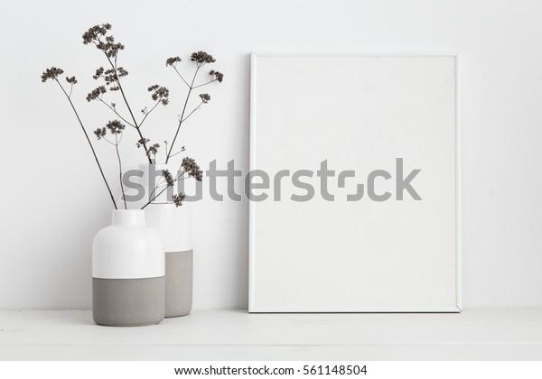 белая рамка макет и сухие веточки в вазе на книжной полке или столе. Белые цвета.