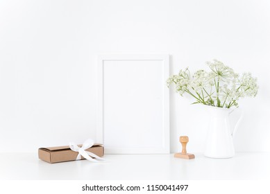 White frame mock up with a herbal in vase, gift box. Mockup for design.Template for businesses, lifestyle bloggers,media