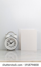 White frame mockup with alarm clock on marble portrait copy space