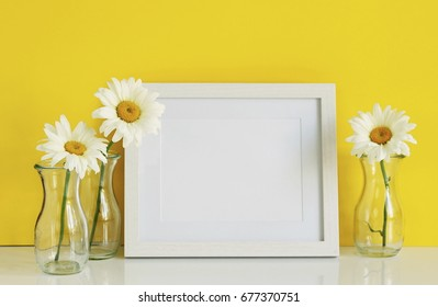 White frame mockup with chamomile flowers in vases on a yellow background. Copy space