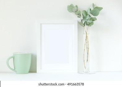 White frame mockup with eucaluptus and mug . Frame mockup. White frame mockup. Poster product design styled mockup. Empty frame mockup.