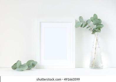 White frame mockup with eucaluptus. Frame mockup. White frame mockup. Poster product design styled mockup. Empty frame mockup.