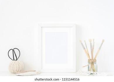 White frame mockup in interior. Frame mock up background for poster or photo frame for bloggers, social media, lettering, art and design. Indoor, frame on table, vintage elements. Summer sea mood