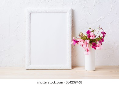 White frame mockup with pink and purple flower bouquet. Empty frame mock up for presentation design.