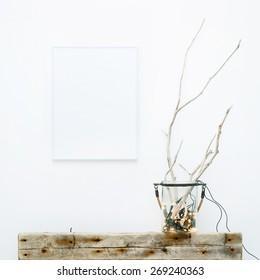 White frame with place for text. Mock up.  Hipster scandinavian style room interior. Jar with garland and weathered brunches. Creative lightning.